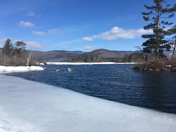 The hills surrounding partially frozen Squam Lake - April